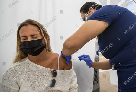 Nurse Maria Ruiz, right, gives a COVID-19 vaccination to Paula Jafif, 41, of Beverly Hills, at Kedren Health on Thursday, April 15, 2021 in Los Angeles, CA. Award-winning television producer, Marti Noxon, who's a big fan of Kedren Vaccines, sent an In-N-Out truck to feed 200+ volunteers who help make this vaccine program such a huge success and she did so on the day that vaccines are being made available to all people 16+ in Los Angeles. (Allen J. Schaben / Los Angeles Times)