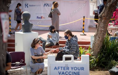 Sidney Campbell, 17, right, of Palos Verdes, waits in the observation area with her mom, Patty Campbell, who already received both COVID-19 vaccinations, after receiving the COVID-19 Vaccination at Kedren Health on Thursday, April 15, 2021 in Los Angeles, CA. Award-winning television producer, Marti Noxon, who's a big fan of Kedren Vaccines, sent an In-N-Out truck to feed 200+ volunteers who help make this vaccine program such a huge success and she did so on the day that vaccines are being made available to all people 16+ in Los Angeles. (Allen J. Schaben / Los Angeles Times)