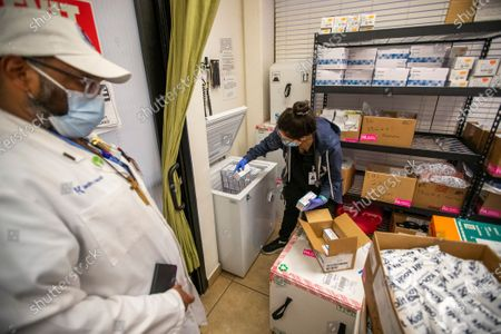 Dr. Jerry Abraham, left, , director of Kedren Vaccines, watches Jasmine Morataya, a physicians assistant at Kedren Health, load Moderna COVID-19 vaccinations into a freezer at Kedren Health on Thursday, April 15, 2021 in Los Angeles, CA. Award-winning television producer, Marti Noxon, who's a big fan of Kedren Vaccines, sent an In-N-Out truck to feed 200+ volunteers who help make this vaccine program such a huge success and she did so on the day that vaccines are being made available to all people 16+ in Los Angeles. (Allen J. Schaben / Los Angeles Times)