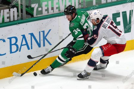 Dallas Stars right wing Denis Gurianov (34) and Columbus Blue Jackets defenseman Michael Del Zotto (15) battle for the puck int he second period during an NHL hockey game, in Dallas