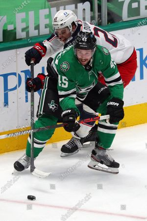 Columbus Blue Jackets' Joshua Dunne (21) and Dallas Stars' Sami Vatanen (45) vie for the puck during the third period of an NHL hockey game, in Dallas