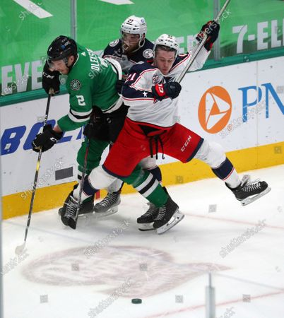Stock Photo of Dallas Stars defenseman Jamie Oleksiak (2) and Columbus Blue Jackets' Stefan Matteau, middle, and Joshua Dunne vie for the puck during the third period of an NHL hockey game, in Dallas