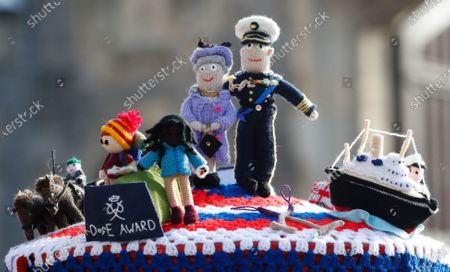 Knitted top cover for a post box depicting Britain's Queen Elizabeth II and her husband Prince Philip in Windsor, England, . Prince Philip husband of Britain's Queen Elizabeth II died April 9, aged 99, his funeral will take place Saturday at Windsor Castle in St George's Chapel. The knitted top show some of Prince Philips favorites: the Royal Yacht Britannia, right, the Duke of Edinburgh award scheme for young people and his hobby of carriage driving