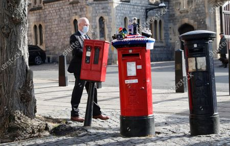 Knitted top cover for a post box depicting Britain's Queen Elizabeth II and her husband Prince Philip is exposed in Windsor, England, . Prince Philip husband of Britain's Queen Elizabeth II died April 9, aged 99, his funeral will take place Saturday at Windsor Castle in St George's Chapel. The knitted top show some of Prince Philips favourite things, the Royal Yacht Britannia, right, the Duke of Edinburgh award scheme for young people and his hobby of carriage driving