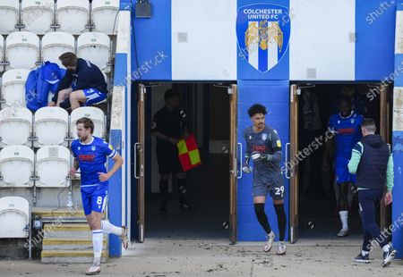 Harry Pell of Colchester United leads Shamal George of Colchester United and the Colchester United team onto the pitch before kick off
