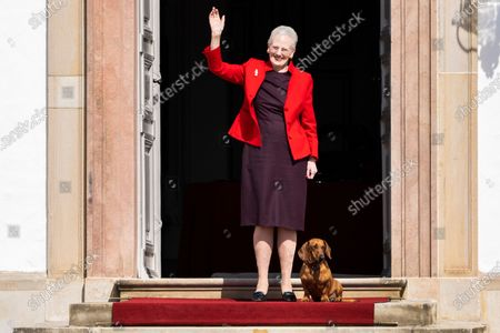 Queen Margrethe II of Denmark is accompanied by one of her dogs as she stands and waves from the steps of Fredensborg Castle, Denmark, 16 April 2021. Queen Margrethe celebrates her 81st birthday on 16 April but public appearences had been cancelled due to the COVID-19 pandemic. The Danish monarch instead came to the outside and waved to people who had decided to pass by her castle. Same as last year the celebrations on her birth annivsary will be small, private and will take place at Fredensborg Castle.