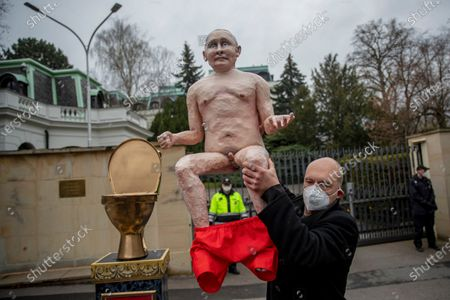 Activists remove a naked statue of Russian President Vladimir Putin sitting on golden toilet bowl during a small protest in front of Russian embassy, in Prague, Czech Republic, 16 April 2021. A few activists placed a pedestal in front of the building of Russian embassy as they protested against the imprisonment of Russian opposition leader and blogger Alexei Navalny, human rights abuses in Russia and Russian aggression against Ukraine.