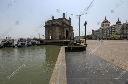 Stock Picture of A general view of deserted Gateway of India and The Taj Mahal Palace hotel, one of the most famous tourist spot, after the curfew imposed to avoid the spread of coronavirus COVID19 disease in Mumbai, India, 16 April 2021. A curfew is announced in Mumbai, and many other states as India recorded its highest daily spike of COVID-19 cases on 14 April with around 200,000 new infections in 24 hours.