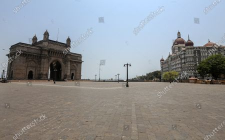 A general view of deserted Gateway of India and The Taj Mahal Palace hotel, one of the most famous tourist spot, after the curfew imposed to avoid the spread of coronavirus COVID19 disease in Mumbai, India, 16 April 2021. A curfew is announced in Mumbai, and many other states as India recorded its highest daily spike of COVID-19 cases on 14 April with around 200,000 new infections in 24 hours.