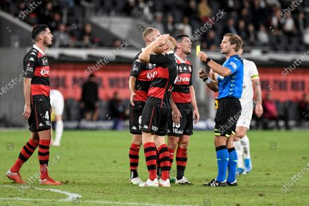 Ziggy Gordon of Western Sydney Wanderers receives a yellow card from referee Alex King as captain Graham Dorrans of Western Sydney Wanderers questions the decision; Bankwest Stadium, Parramatta, New South Wales, Australia; A League Football, Western Sydney Wanderers versus Brisbane Roar.