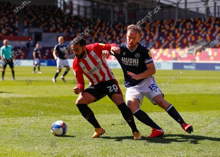 Saman Ghoddos of Brentford is challenged by Alex Pearce of Millwall; Brentford Community Stadium, London, England; English Football League Championship Football, Brentford FC versus Millwall.