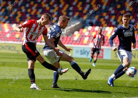 Marcus Forss of Brentford takes a shot past Alex Pearce of Millwall; Brentford Community Stadium, London, England; English Football League Championship Football, Brentford FC versus Millwall.