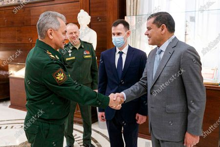 In this handout photo released by Russian Defense Ministry Press Service, Russian Defense Minister Sergei Shoigu, left, shakes hands with Libyan Prime Minister of the Government of National Unity Abdul Hamid Dbeibah in Moscow, Russia