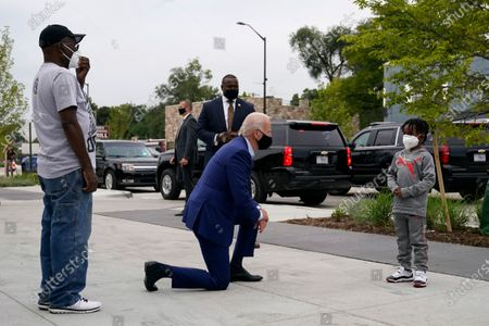 Democratic presidential candidate former Vice President Joe Biden visits with C.J. Brown, right, and Clement Brown, the son and father of the owner of Three Thirteen, as Biden arrives to shop for his grandchildren at the store in Detroit. On, The Associated Press reported on stories circulating online incorrectly claiming a photo shows President Joe Biden kneeling in front of George Floyd's son