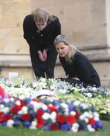 The Countess of Wessex and Lady Louise Windsor, standing, view flowers outside St George's Chapel, at Windsor Castle, Windsor England, ahead of the Saturday funeral service for Britain's Prince Philip. Prince Philip died at the age of 99 on April 9