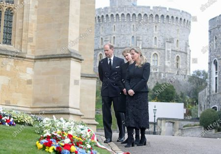Stock Photo of Britain's Prince Edward, Lady Louise Windsor and Sophie Countess of Wessex, left to right, view flowers outside St George's Chapel, at Windsor Castle, Windsor England, ahead of the Saturday funeral service for Britain's Prince Philip. Prince Philip died at the age of 99 on April 9