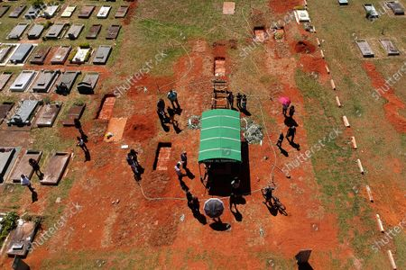 Family members attend the burial service for David Ferreira Gomes, who died from complications related to COVID-19, at the Campo da Esperanca cemetery in Brasilia, Brazil