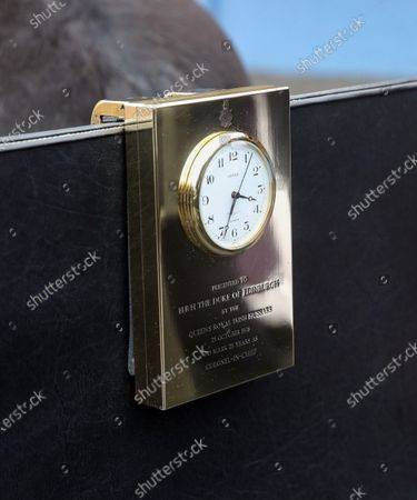 The brass clock given to the Britain's Prince Philip by the Queen's Royal Irish Hussars in 1978, to mark 25 years as Colonel-in-Chief, mounted in the front of his driving carriage at Windsor Castle, England, . The Duke's love of carriage-driving is to be a central feature of his funeral on Saturday when the carriage and ponies will be present with two of his grooms in the Quadrangle of Windsor Castle during the procession. The four wheeled carriage was designed by The Duke of Edinburgh eight years ago