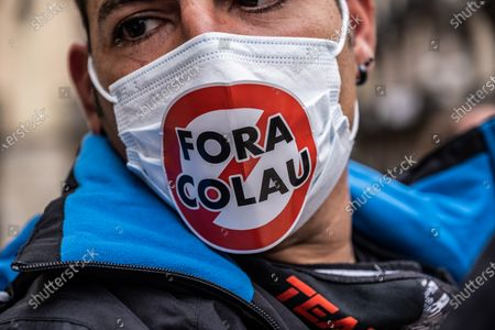 A protester wears a sanitary mask with a sticker calling for the resignation of Mayor Ada Colau during the demonstration.Around 300 people summoned by different civic entities have demonstrated through the streets of Barcelona to the door of the City Hall to request the resignation of the mayor of Barcelona Ada Colau and to show rejection of the municipal policies of urban development and security.
