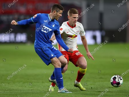 Andrej Kramaric (L) of TSG 1899 Hoffenheim makes a pass whilst under pressure from Dani Olmo of RB Leipzig during the German Bundesliga soccer match between RB Leipzig and TSG Hoffenheim at Red Bull Arena in Leipzig, Germany, 16 April 2021.