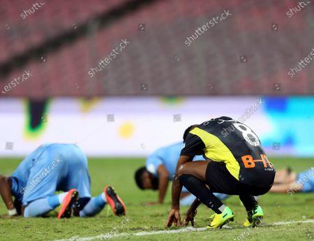 Al-Ittihad's player Fahad Al Muwallad (R) reacts as Al-Batin's players kneel in the background after the end of the Saudi Professional League soccer match between Al-Ittihad and Al-Batin in a draw, at King Abdulaziz Stadium, Mecca, Saudi Arabia, 16 April 2021.