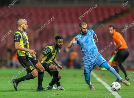 Al-Ittihad's players Muhannad Al-Shanqeeti (C) and Karim El Ahmadi (L) in action against Al-Batin's Youssef El Jebli (R) during the Saudi Professional League soccer match between Al-Ittihad and Al-Batin at King Abdulaziz Stadium, Mecca, Saudi Arabia, 16 April 2021.