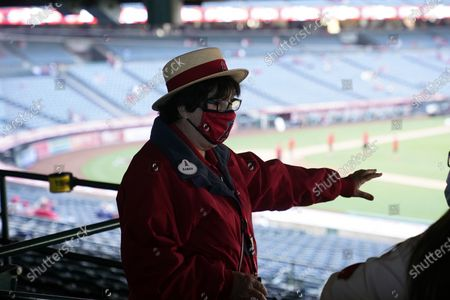 An usher wears a mask while talking to fan amid the COVID-19 pandemic before a baseball game between the Los Angeles Angels and the Minnesota Twins, in Anaheim, Calif