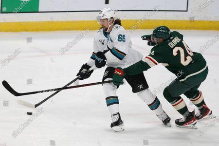 Minnesota Wild's Matt Dumba (24) tries to get after the puck against San Jose's Erik Karlsson (65) during the third period of an NHL hockey game, in St. Paul, Minn. Minnesota won 3-2