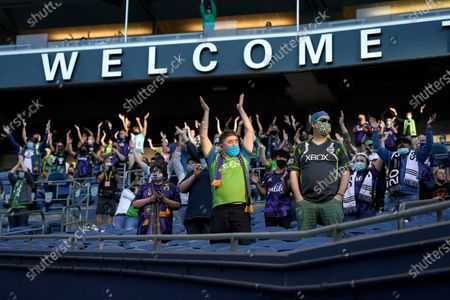"""Fans sitting in socially distanced groups perform the """"Boom Boom Clap"""" cheer at the start of an MLS soccer match between the Seattle Sounders and Minnesota United, in Seattle. The match was the Sounders' home-opener, and the first home game played in front of fans in more than a year"""