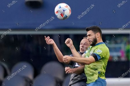 Seattle Sounders midfielder Alex Roldan, right, and Minnesota United defender Chase Gasper, left, vie for a header during the first half of an MLS soccer match, in Seattle