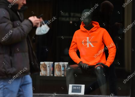 A man walks past a Calvin Klein storefront in Dublin city center, during the COVID-19 lockdown. 