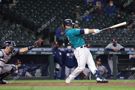 Seattle Mariners' Ty France follows through on a single that drove in the winning run, next to Houston Astros catcher Jason Castro during the ninth inning of a baseball game, in Seattle. The Mariners won 6-5