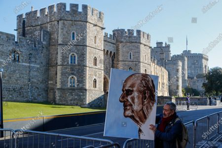 Artist Kaya Mar holds a portrait of Prince Philip ahead of the Prince's funeral in Windsor, England . Philip died April 9 at the age of 99 after 73 years of marriage to Britain's Queen Elizabeth II. Coronavirus restrictions mean there will be only 30 mourners for the service, including the widowed queen, her four children and her eight grandchildren