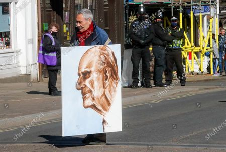 Artist Kaya Mar carries a portrait of Prince Philip ahead of the Prince's funeral in Windsor, England . Philip died April 9 at the age of 99 after 73 years of marriage to Britain's Queen Elizabeth II. Coronavirus restrictions mean there will be only 30 mourners for the service, including the widowed queen, her four children and her eight grandchildren