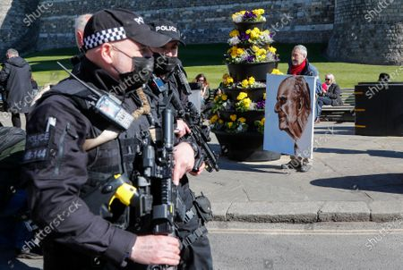 Armed police walk past artist Kaya Mar who holds a portrait of Prince Philip ahead of the Prince's funeral in Windsor, England . Philip died April 9 at the age of 99 after 73 years of marriage to Britain's Queen Elizabeth II. Coronavirus restrictions mean there will be only 30 mourners for the service, including the widowed queen, her four children and her eight grandchildren