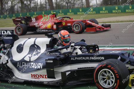 AlphaTauri driver Yuki Tsunoda of Japan leaves his car after crashing as Ferrari driver Carlos Sainz of Spain speeds by during qualifying practice for Sunday's Emilia Romagna Formula One Grand Prix, at the Imola track, Italy