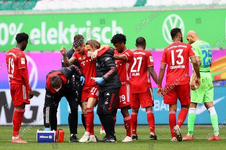 Lucas Hernandez of FC Bayern Muenchen receives medical treatment during the German Bundesliga soccer match between VfL Wolfsburg and FC Bayern Munich at Volkswagen Arena in Wolfsburg, Germany, 17 April 2021.