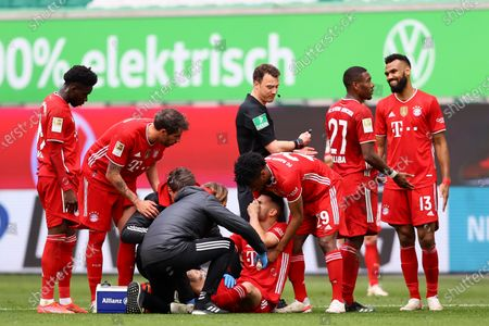 Lucas Hernandez of FC Bayern Muenchen receives medical treatment as teammate Kingsley Coman checks on him during the German Bundesliga soccer match between VfL Wolfsburg and FC Bayern Munich at Volkswagen Arena in Wolfsburg, Germany, 17 April 2021.