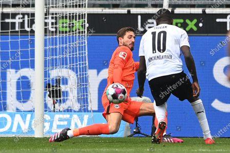 Frankfurt's goalkeeper Kevin Trapp (L) in action against Moenchengladbach's Marcus Thuram (R) during the German Bundesliga soccer match between Borussia Moenchengladbach and Eintracht Frankfurt in Moenchengladbach, Germany, 17 April 2021.