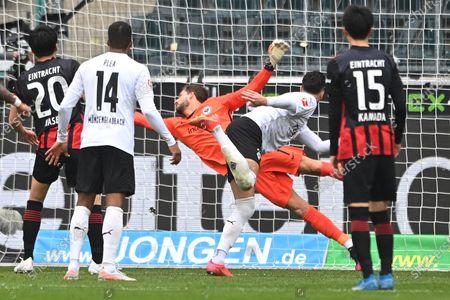 Moenchengladbach's Ramy Bensebaini (2-R) scores the 3-0 lead against Frankfurt's goalkeeper Kevin Trapp (C) during the German Bundesliga soccer match between Borussia Moenchengladbach and Eintracht Frankfurt in Moenchengladbach, Germany, 17 April 2021.