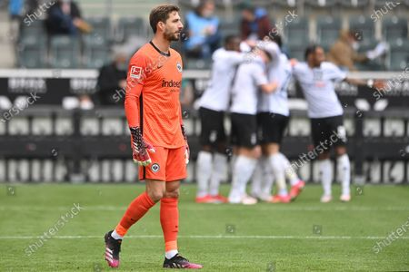 Frankfurt's goalkeeper Kevin Trapp reacts as Moenchengladbach players celebrate their 1-0 lead during the German Bundesliga soccer match between Borussia Moenchengladbach and Eintracht Frankfurt in Moenchengladbach, Germany, 17 April 2021.