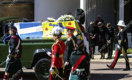 The Duke of Edinburgh's coffin, covered with his Personal Standard, is carried on the purpose built Land Rover Defender, drives past from left Lady Louise Windsor, the Countess of Wessex and James, Viscount Severn with heads bowed, at the Galilee Porch of St George's Chapel, at Windsor Castle, Windsor, England, during the funeral of Britain's Prince Philip. Prince Philip died April 9 at the age of 99 after 73 years of marriage to Britain's Queen Elizabeth II