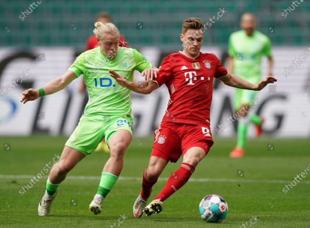 Bayern's Joshua Kimmich, right, and Wolfsburg's Xaver Schlager challenge for the ball during the German Bundesliga soccer match between VfL Wolfsburg and FC Bayern Munich in Wolfsburg, Germany