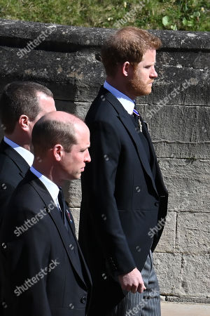 Prince William, Prince William, Peter Phillips and Prince Harry, Duke of Sussex follow Prince Philip, Duke of Edinburgh's coffin during the Ceremonial Procession during the funeral of Prince Philip, Duke of Edinburgh at Windsor Castle on April 17, 2021 in Windsor, England. Prince Philip of Greece and Denmark was born 10 June 1921, in Greece. He served in the British Royal Navy and fought in WWII. He married the then Princess Elizabeth on 20 November 1947 and was created Duke of Edinburgh, Earl of Merioneth, and Baron Greenwich by King VI. He served as Prince Consort to Queen Elizabeth II until his death on April 9 2021, months short of his 100th birthday. His funeral takes place today at Windsor Castle with only 30 guests invited due to Coronavirus pandemic restrictions.