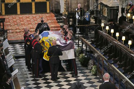 Queen Elizabeth II  (top right) and the Archbishop of Canterbury Justin Welby watch as the Duke of Edinburgh's coffin is carried into St George's Chapel, Windsor Castle