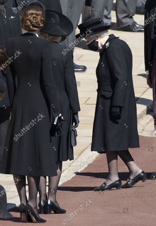 Image Licensed to i-Images Picture Agency. Camilla, Camilla Duchess of Cornwall and Catherine Duchess of Cambridge, Catherine Duchess of Cambridge stand outside St.Georges Chapel as Queen Elizabeth II arrives for the funeral of Prince Philip, The Duke of Edinburgh, at Windsor Castle.
