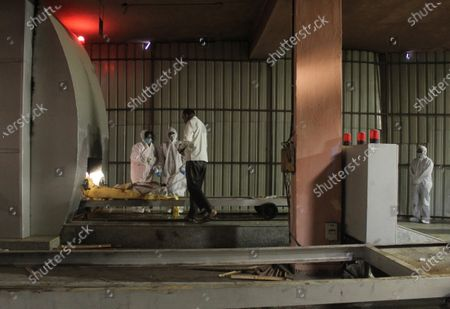 Family members wearing personal protective equipment (PPE) perform the final rites of a person, who died due to the coronavirus disease (COVID-19), at a crematorium in New Delhi, India on April 17, 2021. India on Saturday reported 2,34,692 new Covid-19 cases and 1,341 deaths in the last 24 hours. The global death toll from the coronavirus surged past 3 million people, according to a count by John Hopkins University.