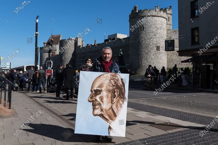 WINDSOR, UNITED KINGDOM - APRIL 17, 2021: Artist Kaya Mar poses with a portrait of the Duke of Edinburgh outside Windsor Castle on the day of the funeral of Prince Philip, the husband of Queen Elizabeth II, who died last week aged 99, on 17 April, 2021 in Windsor, England. The ceremonial funeral of the Duke of Edinburgh will take place entirely within the grounds of Windsor Castle and the public have been asked not to gather there or at other royal residences due to Covid-19 lockdown restrictions.