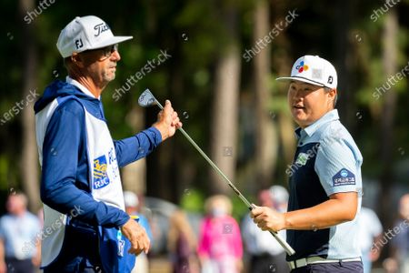 Sungjae Im, of South Korea, hands his putter to his caddie Robert Brown, left, after finishing on the 15th green during the third round of the RBC Heritage golf tournament in Hilton Head Island, S.C