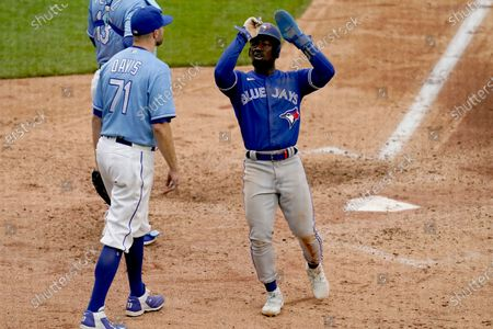 Toronto Blue Jays' Jonathan Davis celebrates as he crosses the plate past Kansas City Royals relief pitcher Wade Davis as he scores on a sacrifice fly hit by Marcus Semien during the seventh inning in the first baseball game of a doubleheader, in Kansas City, Mo. The Blue Jays won 5-1